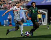 GRENOBLE, FRANCE - JUNE 22: Klara Buehl #19 of the German National Team brings the ball forward as Onome Ebi #5 of the Nigerian National Team defends during a game between Nigeria and Germany at Stade des Alpes on June 22, 2019 in Grenoble, France.