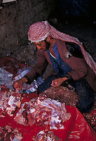A butcher at a street market in Yemen sorts the cuts of meat he sells. Yemen.