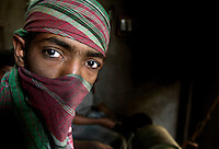 14-year-old Belal covers his face to protect himself from harmful dust while working in a shoe-making factory.