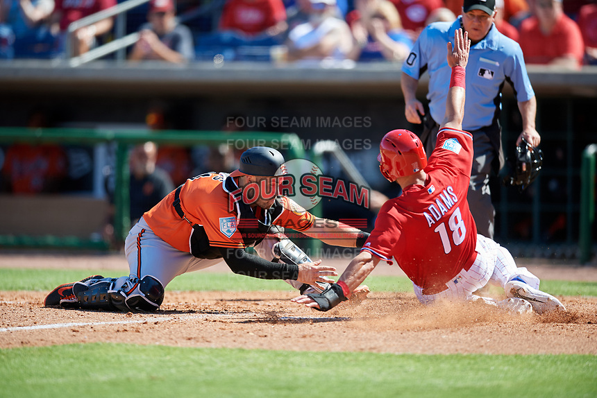 Baltimore Orioles catcher Austin Wynns (61) tags Lane Adams (18) out at home as umpire Tom Hallion looks on during a Grapefruit League Spring Training game against the Philadelphia Phillies on February 28, 2019 at Spectrum Field in Clearwater, Florida.  Orioles tied the Phillies 5-5.  (Mike Janes/Four Seam Images)