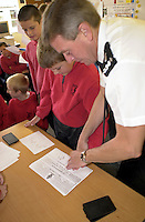 P.C. Dave Horam the youth affairs officer for Kerrier District in Cornwall fingerprinting schoolchildren as part of their science week. The children are given a talk in forensic science. This image may only be used to portray the subject in a positive manner..©shoutpictures.com..john@shoutpictures.com