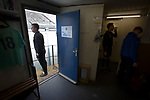 Manager Carl Jarrett (left) at the door to the home dressing room at Mount Pleasant before Marske United take on Billingham Synthonia in a Northern League division one fixture. Formed in 1956 in Marske-by-the-Sea, the home club had secured automatic promotion to the Northern Premier League two days before and were in the midst of a run of six home games in 10 days as they attempted to overtake Morpeth Town to win the league. They won this match 6-1 against already relegated Billingham, watched by a crowd of 196.