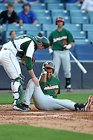 """Miami Hurricanes Harold Martinez #9 is checked on by catcher Daniel Rockhold  #18 after getting hit in the head by a pitch during a game vs. the University of South Florida Bulls in the """"Florida Four"""" at George M. Steinbrenner Field in Tampa, Florida;  March 1, 2011.  USF defeated Miami 4-2.  Photo By Mike Janes/Four Seam Images"""