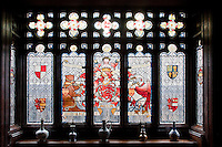 An Arts and Crafts stained glass window with the family coat of arms