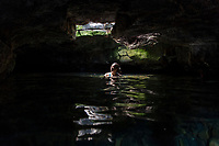 An Asian woman enjoys a fresh water cave at Queen's Bath at Kiholo Bay, Big Island.