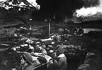 """Japanese attack on Dutch Harbor, June 3, 1942.  Group of Marines on the """"alert"""" between attacks.  Smoke from burning fuel tanks in background had been set afire by a dive bomber the previous day.  Alaska. (Navy)<br /> NARA FILE #:  080-G-12076<br /> WAR & CONFLICT BOOK #:  1147"""