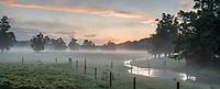 Moody scene of farmland in Whataroa with creek at sunset,  West Coast, South Westland, New Zealand, NZ