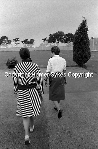 Womens jail 1980s UK. Prisoner and guard walk, exercising in grounds of HM Prison Styal Wilmslow Cheshire England 1986.