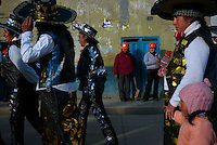 Women with mining helmets look on as children participate in an elementary school parade in the Paragsha neighborhood of Cerro de Pasco, Peru.