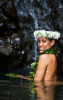 Beautiful Hawaiian woman takes a dip next to a waterfall in Waimano Pool at the end of Manana Ridge Trail