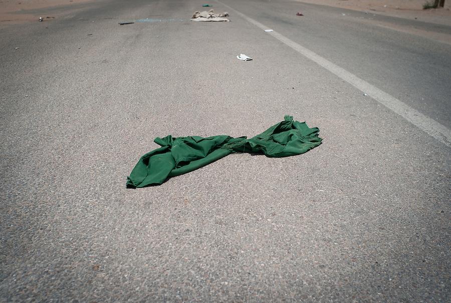 A green Gaddafi flag lies on the road leading to Zawiya near Bir Ayad, Libya.