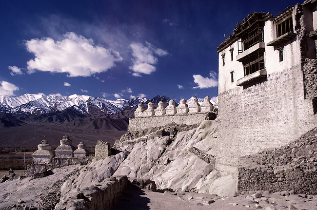 CHORTENS and the buildings of SHEY GOMPA (monastery), sit beneath HIMALAYAN PEAKS - LADAKH, INDIA.