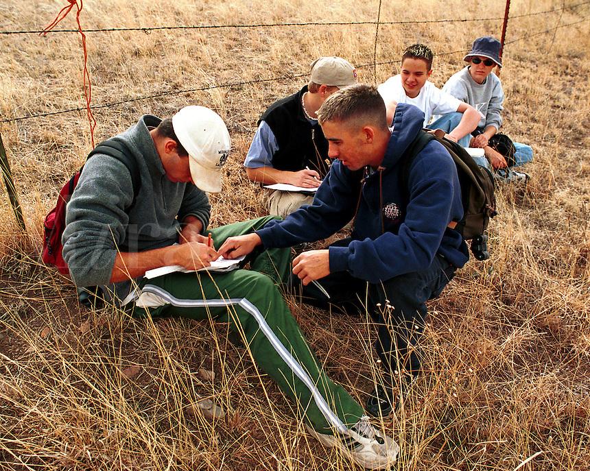 Orienteering classroom outdoors - teenage male students plotting a course on orienteering hike. High School Students. Arizona.