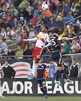 New York Red Bulls forward Andre Akpan (15) and New England Revolution defender Stephen McCarthy (15) battle for head ball.  In a Major League Soccer (MLS) match, the New England Revolution (blue) tied New York Red Bulls (white), 1-1, at Gillette Stadium on May 11, 2013.