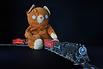 Hand made teddy bear rides classic, antique, electric train out of the dark.
