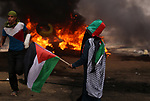 A Palestinian woman waves the national flag during clashes with Israeli security forces in tents protest where Palestinians demanding the right to return to their homeland, at the Israel-Gaza border, in Khan Younis in the southern Gaza Strip, on May 4, 2018. Photo by Yasser Qudih