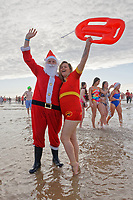 Pictured: A man in a Santa outfit embraces an RNLI volunteer. Wednesday 25 December 2019<br /> Re: Hundreds of people in fancy dress, have taken part in this year's Porthcawl Christmas Swim in south Wales, UK.