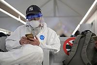 IVORY COAST, Abidjan, airport, chinese traveller with protection wear during Corona Pandemic time at gate on flight to Paris / ELFENBEINKÜSTE, Abidjan, Flughafen, Chinesische Reisende in Schutzkleidung während der Corona Pandemie