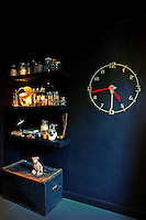 A small lamp and glassware is arranged on shelves above a blue painted chest. Next to it a modern skeleton clock is fixed to the wall.