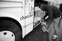 Milan - San Remo 2013: the iced edition.soigneur Raoul Saren the-rows some wet clother into the teambus dryer so that the riders clothes may be re-used for the 2nd start