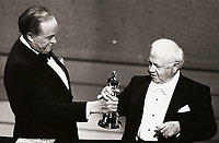 Mickey Rooney is presented with an Honorary Oscar by Bob Hope at the 55th Annual Academy Awards, 1983.