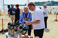 BNPS.co.uk (01202 558833)<br /> Pic: Graham Hunt/BNPS<br /> <br /> Town Mayor Cllr Colin Huckle gets a coffee at the end of the meeting.<br /> <br /> Town hall officials swapped their stuffy chambers for the sand and sea today as they took part in what is thought to be the UK's first ever council meeting on a beach.<br /> <br /> Weymouth Town Council in Dorset held the event on the beach in protest at the Government banning virtual meetings.<br /> <br /> Since May 6, votes cast at virtual council meetings have not been legally binding following a controversial ruling upheld by a High Court judge.<br /> <br /> But because social distancing is difficult to practice in many town halls, officials in Weymouth used a loophole in the rules to meet on a beach.