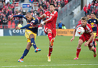 Toronto, Ontario - May 17, 2014: New York Red Bulls forward Thierry Henry #14 attempts a shot on goal as Toronto FC midfielder Jonathan Osorio #21 tries to defend during the second half in a game between the New York Red Bulls and Toronto FC at BMO Field. Toronto FC won 2-0.