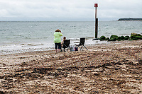 BNPS.co.uk (01202 558833)<br /> Pic: MaxWillcock/BNPS<br /> <br /> Pictured: A couple set up their beach chairs beside the mass of rotten seaweed.<br /> <br /> A south coast beach has become a no-go zone at the height of the summer holidays after a mass of rotten seaweed was allowed to fester on the sand.<br /> <br /> The vast carpet of kelp has been left to gather on Avon Beach in Christchurch, Dorset, for over a month.<br /> <br /> The unpleasant mess is attracting flies and is putting people off visiting the beauty spot which is normally hugely popular with families.<br /> <br /> Bathers are having to wade through the sticky seaweed to get to the sea and are usually left with their legs covered in it.