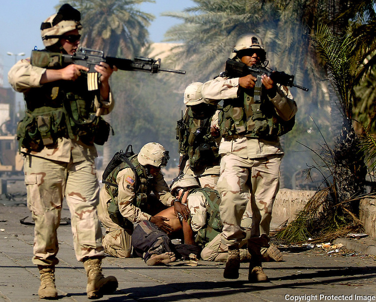 1st Cavalry Division soldiers arrest an Iraqi at the scene of a car bomb.  The crowd became too hostile and the troops had to pull back before more soldiers arrived in riot gear.  A suicide car bomb detonated in central Baghdad during rush hour as a convoy of three SUV pass near Tahrir Square.  At least 12 are killed and at least 40 others wounded.  Among the dead were 5 foreign nationals.  Photo taken Monday, June 14, 2004..Star-Telegram/Khampha Bouaphanh