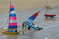 People setting up catamarans on the beach, Brittany, France.