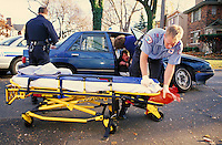 Emergency medical technicians (EMT's or paramedics) at scene of auto accident preparing stretcher, Detroit, MI. Policeman. Detroit Michigan.
