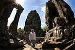 A female Western tourist stands inside the ruins of the Bayon Temple in the ancient city of Angkor, in northwestern Cambodia, where Khmer kings established their capitals from the ninth to the 15th century.