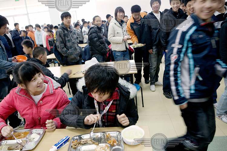 """Students having lunch in their canteen at the Qingdao City Sports School, one of the country's top breeding grounds for Olympic athletes. Principal Qiao Xiangdong credits the Beijing 2008 Olympic Games for spurring the local government to build a USD 42 million new campus for the academy's 600 students. """"Before, some parents were worried about sending their kids to sports schools because they thought their children would have to eat too much bitterness,"""" Qiao says, using the Chinese term for enduring hardship. """"But the Olympic Games have made people willing to contribute to the nation's glory."""""""
