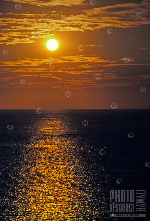 A golden pathway of the setting sun reflected on ripples in the Pacific Ocean off the Kona coast. Golden clouds and sky frame a blazing white sun.