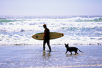 Long Beach, Pacific Rim National Park Reserve, Vancouver Island, BC, British Columbia, Canada - Surfer surfing with Pet Dog