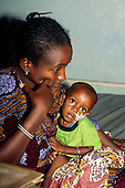 Gambia. Woman with sick baby, who has a nasal tube.
