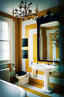 A traditional styled bathroom with a modern graphic design in the yellow and white tiled walls. A mirror is placed above a pedestal washbasin.