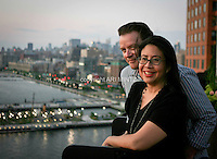 Tenth anniversary of 9/11.  Rebuilding at the World Trade Center site.  Longtime Lower Manhattanites Celeste Lee and Gerald Janssen survived 9/11.  They watch sunset from their roofdeck near Ground Zero.  Photo by Ari Mintz.  8/8/2011.