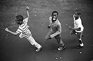 Manhattan, New York City, NY. July 1966. <br /> Three kids running enthusiastically on the streets of Harlem next to the Jazz Mobile, which has been abandonned ever since. It slowly drove in the streets of Harlem and brought  a little joy the people on the sidewalks.<br /> <br /> New York City, Harlem, Juillet 1966: Trois jeunes suivent avec enthousiasme le programe: Jazz Mobile qui a ete abandonne depuis. C'etait un camion qui parcourait lentement les rue d'Harlem l'été pour apporter un peu de joie sur les trottoirs!