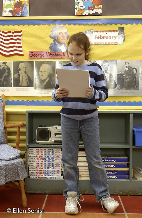 MR / Schenectady, NY.Yates Arts-in-Education Magnet Schl (urban elementary schl) Grade 4 girl (9) gives a speech she has written as part of American history unit on United States presidents. Behind her is a President's Day bulletin board with photos and information about George Washington and Abraham Lincoln..MR: Goo5.©Ellen B. Senisi