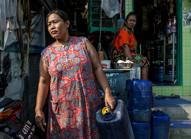 13 August 2019, Jakarta, Indonesia: Ibu Mar (49) doing her laundry by hand with water brought in plastic barrels outside her home in Muara Baru, North Jakarta. She is speaking about the lack of water facilities that the local poor population has access to. Water is hauled in each day by motorcycle and trucks and by hand to allow residents of the kampungs (village) to buy it for washing and to do laundry. Separate water is needed for drinking. The Jakarta Governor is proposing a program to send in trucks of water for the locals to get for free to ease their plight. They are living in villages below the seawater line on the coast of Jakarta that is sinking faster than anywhere else in the world.They have the position of being surrounded by water yet not having access to clean supplies. Picture by Graham Crouch/The Australian