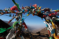 Tibetan prayer flags flutter in the wind at a shrine on the Qinghai-Tibetan Plateau. China
