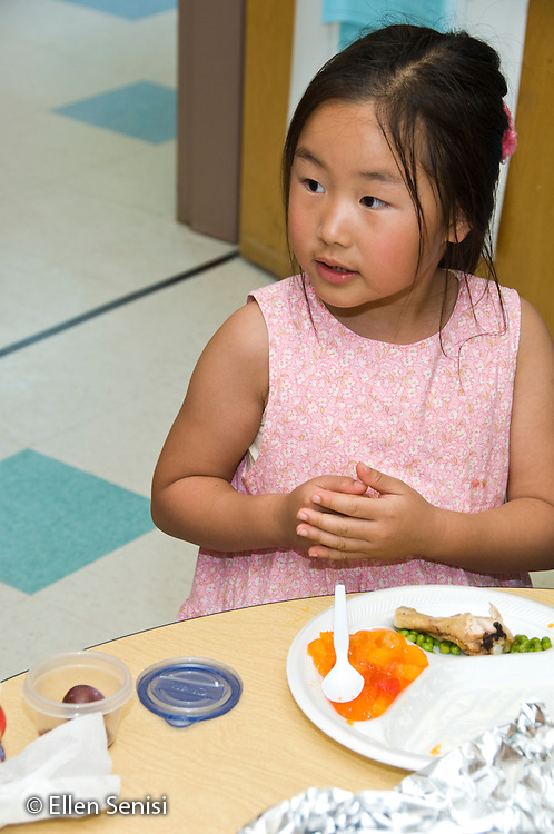 MR / College Park, Maryland.Center for Young Children, laboratory school within the College of Education at the University of Maryland. Full day developmental program of early childhood education for children of faculty, staff, and students at the university..Girl (5) sits at table eating healthy lunch of fruit, peas, and chicken..MR: Kim6.© Ellen B. Senisi