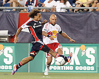 New England Revolution defender Kevin Alston (30) late and fails to block New York Red Bulls midfielder Joel Lindpere (20) passes the ball. In a Major League Soccer (MLS) match, New England Revolution defeated New York Red Bulls, 2-0, at Gillette Stadium on July 8, 2012.