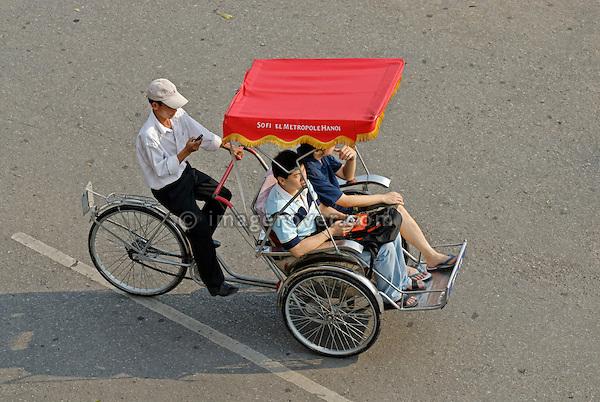 Asia, Vietnam, Hanoi. Hanoi old quarter. Cyclo driver using his mobile phone while driving some tourists through Hanoi.