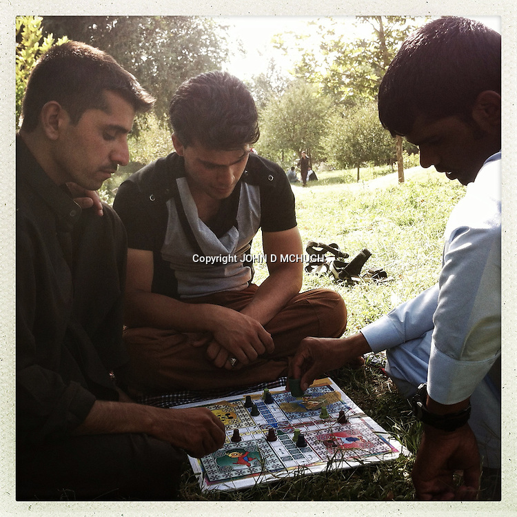 ** TO GO WITH AFGHANISTAN STORY FOR PETER MURTAGH - NO ARCHIVE, NO RESALE ** Young Afghans play a board game in Babur Gardens, Kabul,21 August 2012. (John D McHugh)
