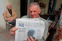 Brescia / Italia - giugno 2013<br /> Pierino Antonioli, contadino bresciano di 70 anni, abita nell'area inquinata dal PCB prodotto dall'industria chimica Caffaro. A causa dell'inquinamento non può coltivare i campi messi sotto sequestro dall'autorità giudiziaria. Nella foto Antonioli mostra un giornale locale che sottolinea i pericoli per la salute derivanti dagli alimenti coltivati e prodotti nel bresciano. Sullo sfondo la signora Molini Luigia (93) madre di Pierino Antonioli.<br /> Foto Livio Senigalliesi