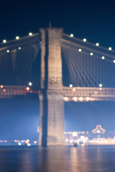 Soft Focus/Defocused View of Brooklyn Bridge and East River Illuminated at Night, New York City, New York State, USA
