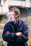 Man smoking pipe,face lost in cloud of smoke at market in small rural village near Wuxi, Chongqing Area, China, Asia