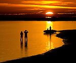 Kayakers and beach goers watch the sunset at Shell Point Beach in Wakulla County, Florida along the Florida panhandle.